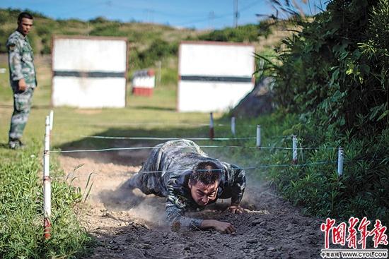 庙子湖岛部队训练场,战士冉同同在课目400米障碍中过铁丝网.