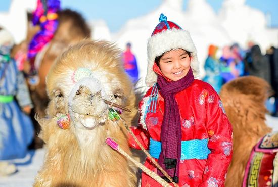 1月9日,一名蒙古族小朋友和骆驼合影。当日,内蒙古苏尼特右旗第12届骆驼文化节在苏尼特右旗赛汉塔拉镇举行。来自鄂尔多斯、呼伦贝尔及苏尼特和乌珠穆沁草原的牧民带着200多峰骆驼在白雪覆盖的草原上进行骆驼选美、骆驼竞速等比赛。文化节还举行了赛马、搏克等蒙古族传统体育活动。 新华社记者 连振/摄