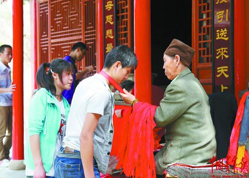 陈玉梅 会宁/会宁桃花山上,考生烧完香,72岁的陈玉梅照例赐给每人一个红布...